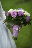 Bridal bouquet of purple and white roses in bride's hands Royalty Free Stock Images