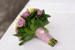 Bridal bouquet of purple and white roses on the table Royalty Free Stock Image