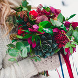 Bridal bouquet with red and burgundy colors. Unusual wedding bouquet with succulent flowers in retro style at hands of a bride Royalty Free Stock Images