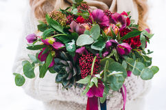 Bridal bouquet with red and burgundy colors. Unusual wedding bouquet with succulent flowers in retro style at hands of a bride Stock Photography
