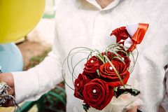 Bridal bouquet of red roses in the hands of groom stock image