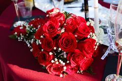 Bridal bouquet of red roses on table. A bride`s bouquet of red roses and white baby`s breath flowers is lying on a table at a wedding reception.  Tablecloth is Royalty Free Stock Images
