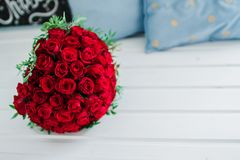 Bridal bouquet of red roses on a white wooden table royalty free stock photos
