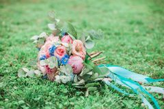 Bridal bouquet with ribbon lies on grass stock image