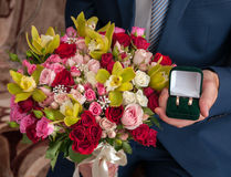 Bridal bouquet and the ring in the hands of the groom Royalty Free Stock Photos