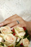Bridal bouquet and rings. Female hand wearing wedding rings and holding bridal bouquet Stock Photo