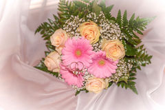 Bridal bouquet with rings on peach roses and pink gerberas Royalty Free Stock Images