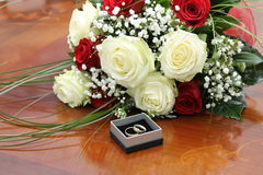 Bridal bouquet and rings. Bridal bouquet of red and white roses and rings Royalty Free Stock Images