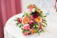 Bridal bouquet of roses, buttercups and other flowers Stock Photo