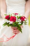 A bridal bouquet of roses in hands of the bride Royalty Free Stock Photo