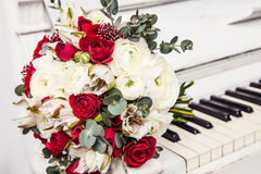 The bridal bouquet from roses lies on piano keys. Stock Photography