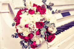 The bridal bouquet from roses lies on piano keys. Stock Images