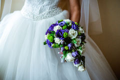 Bridal bouquet of roses. Bridal bouquet of white and purple flowers, in the hands of the bride Royalty Free Stock Photography