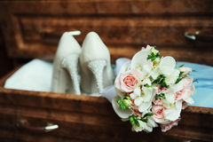 Bridal bouquet and shoes. Gentle wedding bouquet in the foreground and beautiful shoes with heels in the drawer Royalty Free Stock Photography