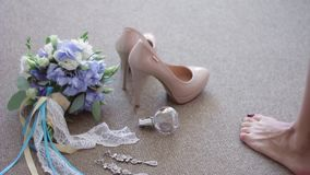 Bridal bouquet, shoes, jewelry, perfumes lying on the floor. The bride goes and picks up from the floor, leaving shoes stock video