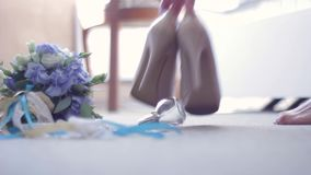 Bridal bouquet, shoes, jewelry, perfumes lying on the floor. The bride goes and picks up from the floor, leaving shoes stock footage