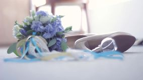 Bridal bouquet, shoes, jewelry, perfumes lying on the floor. The bride passes by can see only their feet in the stock video