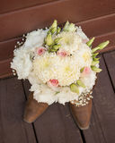 Bridal bouquet sitting on top of cowgirl boots Stock Photo