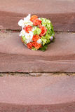 Bridal bouquet on stairs. Orange, white and green bridal bouquet on stone stairs stock image
