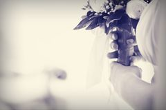 Bridal bouquet. Tender bridal bouquet; hands holding a bouquet; space for writing. The image could be used for invitation card for bridal party or for wedding Stock Photography