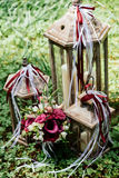 Bridal bouquet and three wooden lantern with candles stand. On the grass Royalty Free Stock Photo