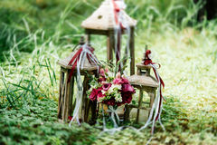 Bridal bouquet and three wooden lantern with candles on th. Bridal bouquet and three wooden lantern with candles stand on the grass Royalty Free Stock Photo