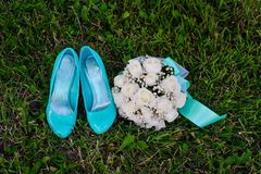 Bridal bouquet and turquoise shoes on green grass Royalty Free Stock Image
