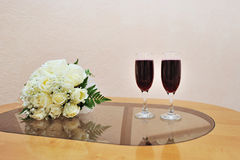 Bridal bouquet and two glasses of wine on the table Royalty Free Stock Photo