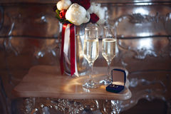Bridal bouquet and wedding rings in the box with two glasses of champagne Royalty Free Stock Photos