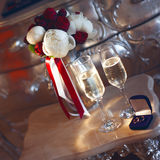 Bridal bouquet and wedding rings in the box with two glasses of champagne Stock Photography