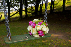 Bridal bouquet and wedding rings on a swing Stock Image