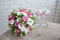 bridal bouquet with wedding rings and  wine glasses on the table in the morning of the  day Stock Photo