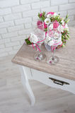 bridal bouquet with wedding rings and  wine glasses on the table in the morning of the  day Stock Photography