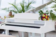 Bridal bouquet on a white piano Stock Photo