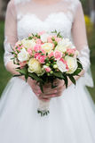 Bridal bouquet with white and pink roses. The bride in white wedding dress holds a wedding bouquet with white and pink ro Royalty Free Stock Image