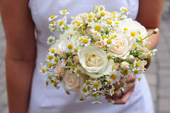 Bridal bouquet. Of white roses and daisies held in the hands Royalty Free Stock Photo