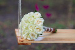 Bridal bouquet of white roses on a swing. Bridal bouquet of white roses lay on a swing Stock Images