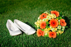 Bridal bouquet and white shoes bride lying on the grass Royalty Free Stock Image