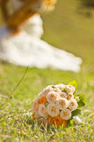 Bridal bouquet and white wedding dress on Royalty Free Stock Photos