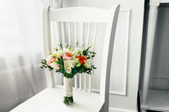 Bridal bouquet on the white wooden chair. Close-up. Indoors Royalty Free Stock Images