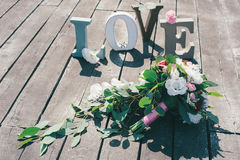 Bridal bouquet on wooden. Boards with volumetric letters love Royalty Free Stock Image
