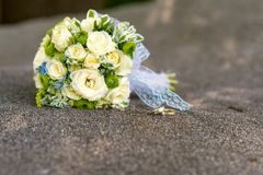 Bridal bouquet of yellow roses and wedding rings over gray stone. Close up royalty free stock image