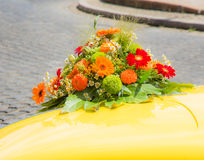 Bridal bouquet on a yellow wedding car Royalty Free Stock Images