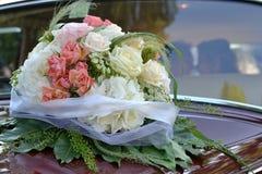 Bridal bukiet przy ślubnym samochodem Zdjęcia Royalty Free