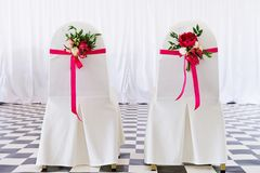 Bridal chairs decorated with flowers. Photo taken inside a wedding tent Stock Photos