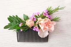 Bridal comb decorated with fresh flowers. On white wooden table Stock Photo