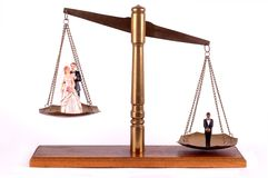 Bridal couple and bachelor on brass scale. Bridal couple and bachelor unbalanced on a brass scale royalty free stock images