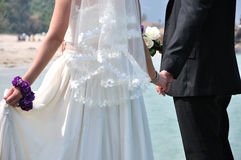 Bridal couple in the beach. New married couple in the beach with wedding dress and bouquet, and hands together, shown as new couple in happy holiday and love Royalty Free Stock Images