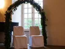 Bridal couple chairs under trellis arch. An ivy trellis arch and white decorated chairs in front of a piano in the wedding hall of a castle - a decorative Royalty Free Stock Images