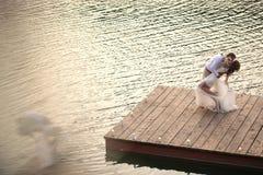 Bridal couple embracing on a bridge near the lake. Groom kissing his bride on a bridge near the lake Stock Image